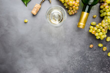 Glass Of White Wine And Ripe Grapes On Gray Background, Top View