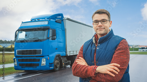 Happy Professional Young Truck Driver Crosses Arms and Smiles on Camera. Behind Him Parked Blue Long Haul Semi-Truck with Cargo Trailer
