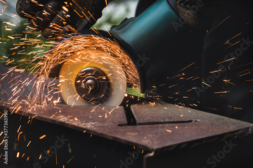 Tablou Canvas grinding cutting metal sheet with angle grinder machine and sparks, Close up