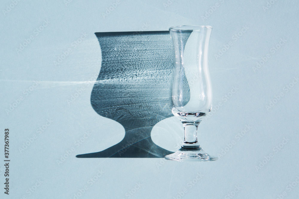 Fototapeta A small transparent and glass wine glass or glass lies on a blue background. Beautiful shade from sunlight.