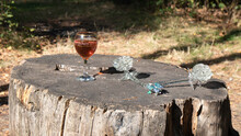 A Glass Of Rose Wine And  Wonderful Vintage  Crystal Rose As Decoration Are On The Old Stump.  The Glass   Wine  Is Lighted  By Sunlight Against The Background Of A Dark Wet Forest.