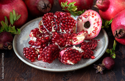 Fotografiet Fresh juicy pomegranate - whole and cut, with leaves on  table