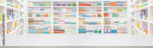 Empty wood counter top with pharmacy drugstore shelves blur pharmaceutical medicine product background - 377381381