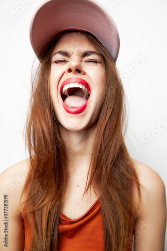 Photo Woman with a cap with closed eyes opens his mouth wide emotions on her head red