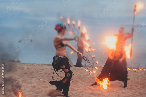 Vászonkép Group of fire artists fakir perform amazing show at night with flamethrowers, fi