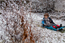 Little Boy On A Sled In A Light Snow