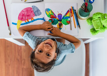 High View Of A Little Girl Sitting On The Table And Painting Pictures Of Animals.