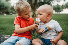 Boy Sharing His Ice Cream With His Little Brother
