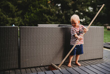 Young Male Child Barefoot Sweeping Backyard Patio With Big Broom