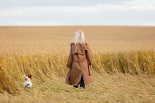 Blonde Woman In Cloak With Dog Is Walking In Wheat Field