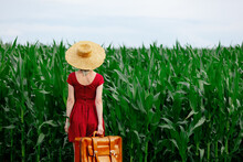 Blonde Lady In Hat And Beautiful Red Dress With Suitcase In Corn