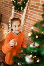 Teenage Girl Decorating Christmas Tree