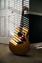 Acoustic Guitar Against A Wall