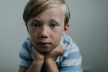 Pensive Little Blond Boy Looking At The Camera