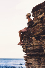 Man Sitting On Rocky Outcrop