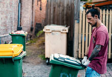 A Young Hipster Young Male Concerned About Environment Is Pushing The Full Rubbish Wheelie Bins On T