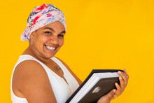 Smiling Woman With Book On Coloured Yellow Background