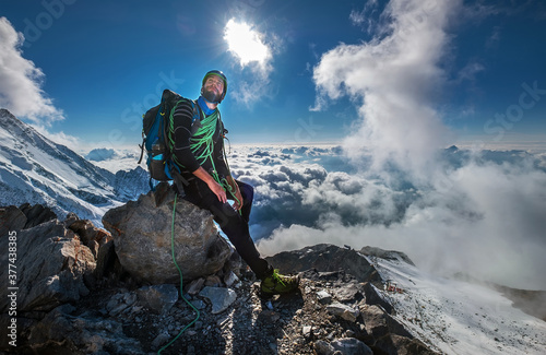 Climber in a safety harness, helmet, and high mountaineer boots with picturesque Tapéta, Fotótapéta