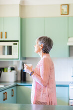 Older Woman Standing In Kitchen Holding A Cuppa Tea