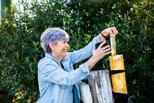 Senior Woman Checking Rain Gauge On Fence