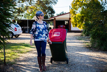 Middle Aged Woman Taking Rubbish Bin Out For Collection