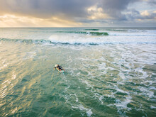 Looking Down On A Lone Surfer Paddling Into Waves Under A Darkening Sky