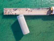 Aerial View Of Fishermen And Tourists On An Ocean Jetty And Boat Shed