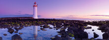 A Lighthouse Reflected In Rock Pools Against A Purple Dawn Sky