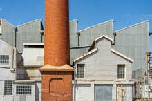 A Tall Brick Chimney Beside A Large Tin Factory