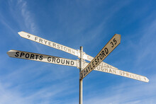 Looking Up At  Road Sign With Long Directional Arms, Against A Blue Sky