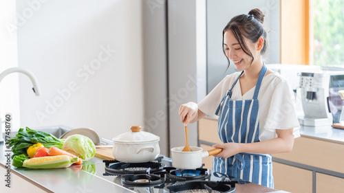 Carta da parati キッチンで料理をする女性