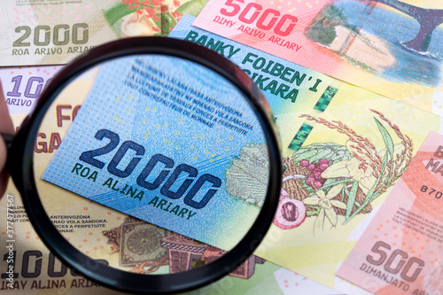 Fotografering Currency of Madagascar in a magnifying glass a business background
