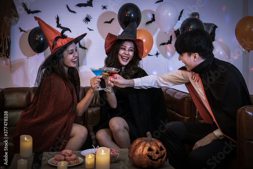 Fotografie, Obraz Young happy Asian people dressing Halloween costume, vampire and witch, celebrating in party