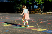 Cute Little Toddler Girl Playing Hopscotch Game Drawn With Colorful Chalks On Asphalt. Little Active Child Jumping On Playground Outdoors On A Sunny Day. Summer Activities For Children.