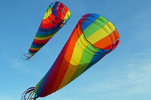 Close-up Of Two Huge Colorful Wind Kite Tubes Flying In The Wind On A Sunny Day With A Blue Sky