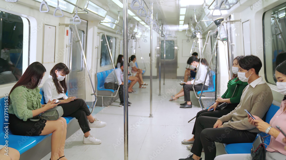Fototapeta Crowd of people wearing face mask on a crowded public subway train travel . Coronavirus disease or COVID 19 pandemic outbreak and urban lifestyle problem in rush hour concept .