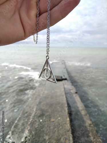 Fotografering In the photo the symbol of the deathly Hallows on the background of the sea