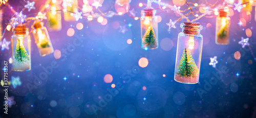 Fototapeta Abstract Christmas Card With Defocused Vintage Effects - String Light With Trees In Glass Jars Decoration obraz