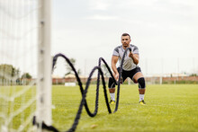 Soccer Player Doing Exercises On The Field. He Is Doing Exercises With Battle Ropes.