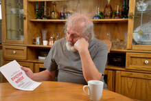 Frustrated Old Man Sitting And Reading The Eviction Notice He Just Received..