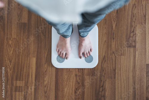 Obraz Top view, woman standing on body scale, checking body weight, dieting, lose and gain weight concept - fototapety do salonu