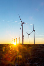 Wind Turbines At Dusk. Landscape Sunset With Windmills. Renewal Source Of Electricity. Wind Turbines Field New Technology For Clean Energy On Mountain, Sunset View With Colorful Twilight On Sky