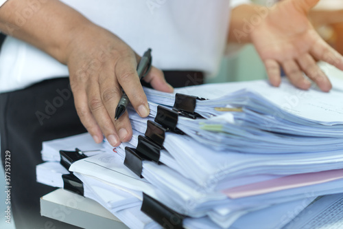 Fototapeta Stacks of lot documents report papers with clips waiting be managed by office workers arranging on desk in busy office. Concept of workload in business finacial paperwork information or investigate obraz