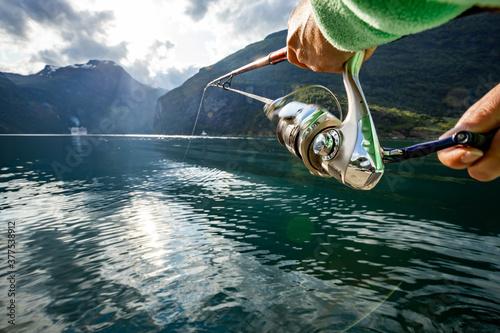 Fototapeta Woman fishing on Fishing rod spinning in Norway.