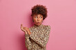 Young stylish pretty woman with Afro hair looks surprisingly aside, keeps mouth opened and rubs hands. Shocked beautiful elegant lady in fashionable leopard outfit poses against pink background