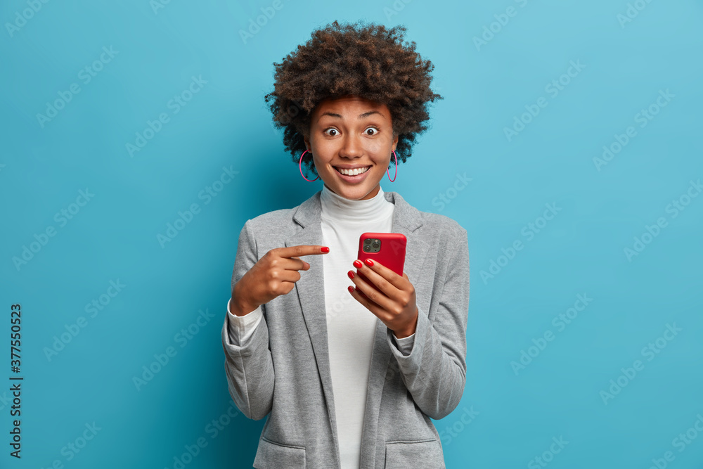 Fototapeta Joyful surprised woman employee opens calendar on mobile phone for planning appointment, points at smartphone display and wears formal outfit. Female office worker happy to check balance on salary day