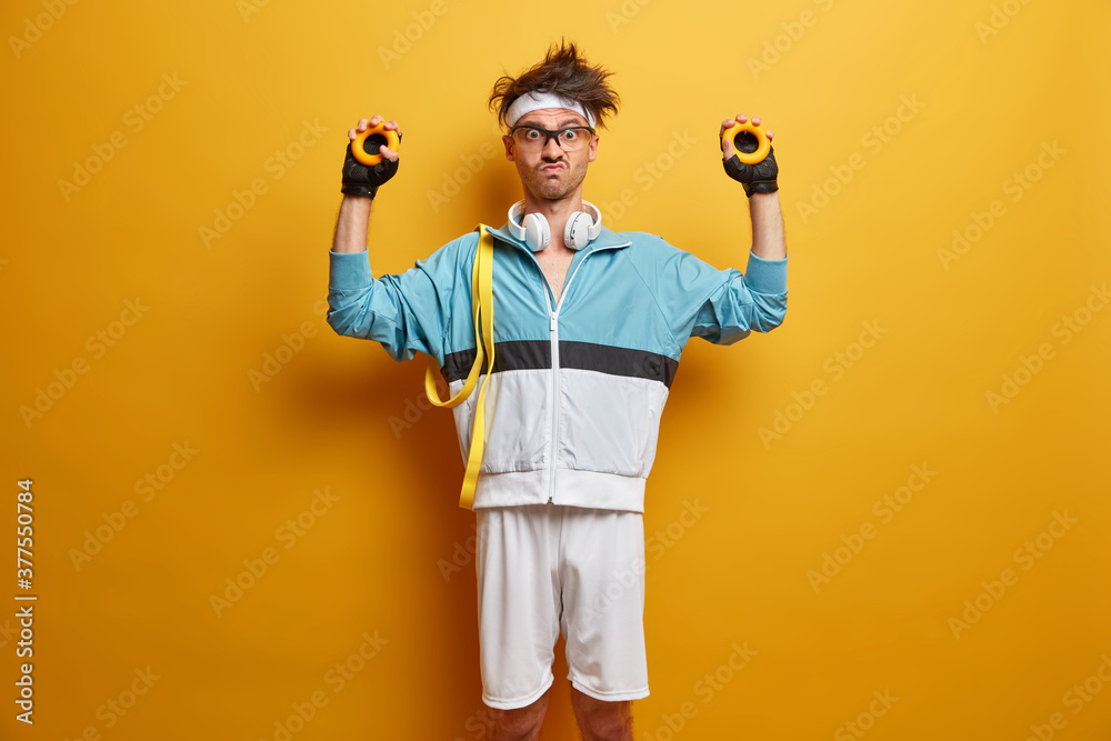 Fototapeta Indoor shot of serious man goes in for sport regularly and squeezes round expander, wears headphones on neck. Motivated sportsman gains muscles, stands against yellow background. Sporty athletic guy