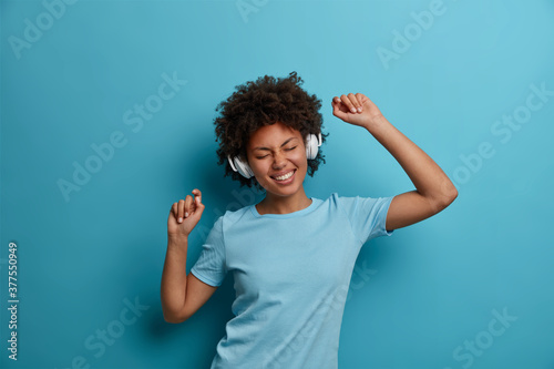 Carefree joyful young woman with Afro hair listens cool new favorite song in stereo headphones and dances carefree, closes eyes in pleasure Fototapet