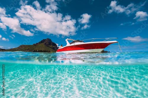 Fototapeta Tropical ocean water with sandy bottom and motor boat