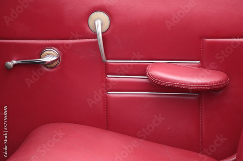 Interior of a classic car, door trimmed in red leather with manual controls for Canvas Print